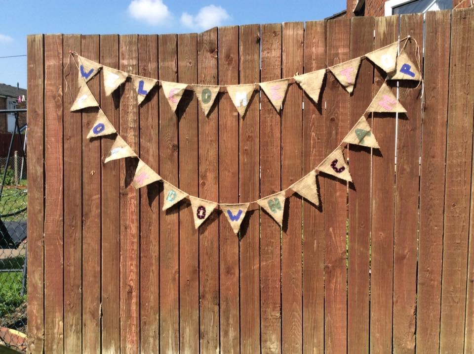 """Homemade bunting on a fence that says """"welcome to lockdown camp"""""""