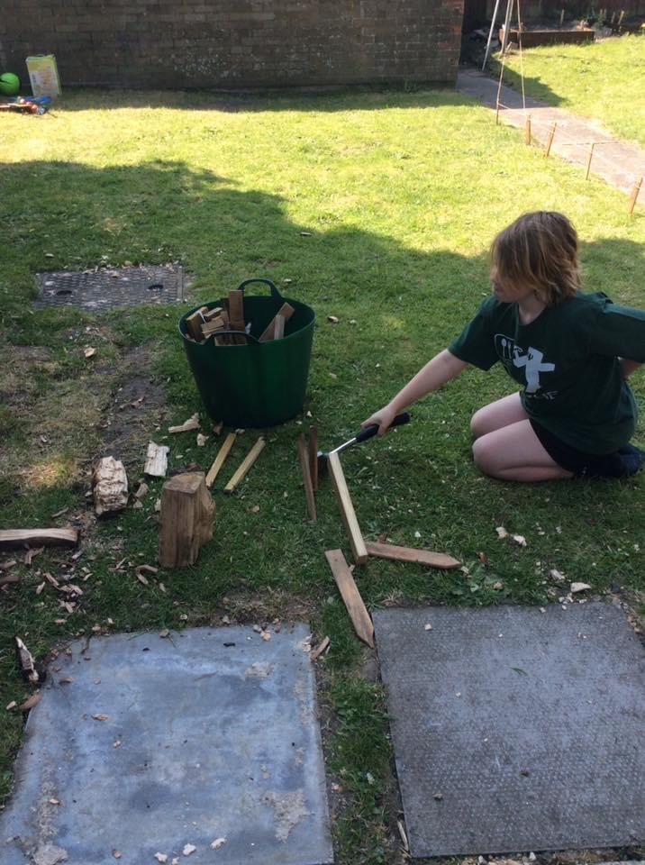 photo of young person learning to split wood